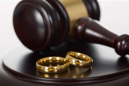 divorcio: Primer plano de anillos de boda y martillo de madera