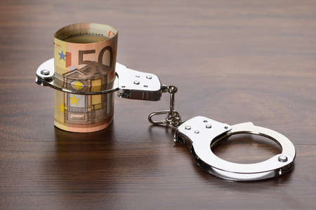 criminal act: Close-up Of Euro Notes With Handcuffs On Wooden Table Stock Photo