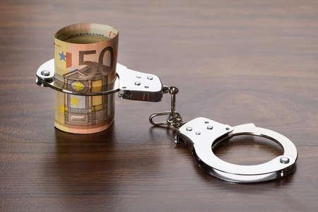 delito: Primer plano de billetes de euro con las manillas en la tabla de madera Foto de archivo