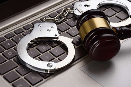 Close-up Of Gavel And Handcuffs On Laptop
