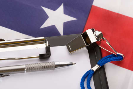 international basketball: Metal Sport Whistle With Pen And Paper Sheet On American Flag