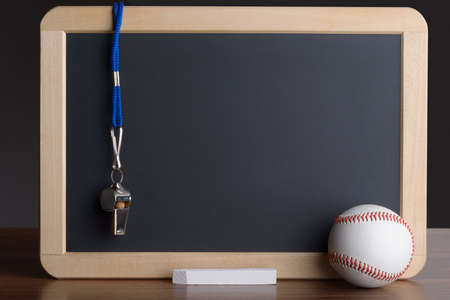 Close-up Of Slate With Baseball; Chalk And Whistle