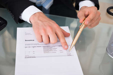 account executive: Businessmans hands pointing at invoice in office Stock Photo