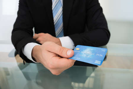 man holding card: Midsection of businessman giving credit card at desk in office