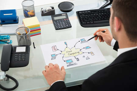 Cropped image of businessman drawing cloud computing chart at desk in office photo