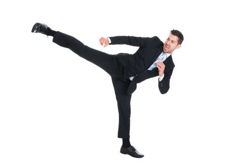 Full length of young businessman kicking over white background Stock Photo