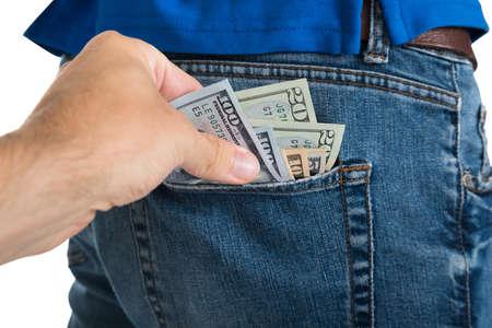흰색 배경 위에 다시 주머니에서 돈을 빼내는 도둑의 근접 촬영 스톡 콘텐츠