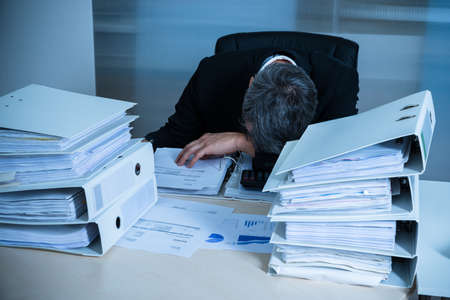 pile of paper: Exhausted Businessman Sleeping At Desk In Office Stock Photo