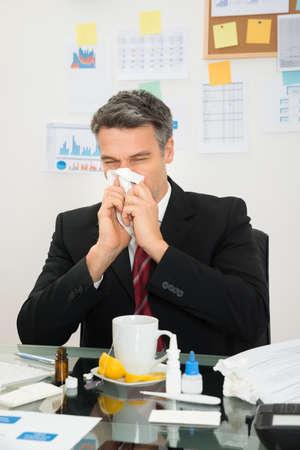 Mature Businessman At Office Desk Blowing His Nose Foto de archivo