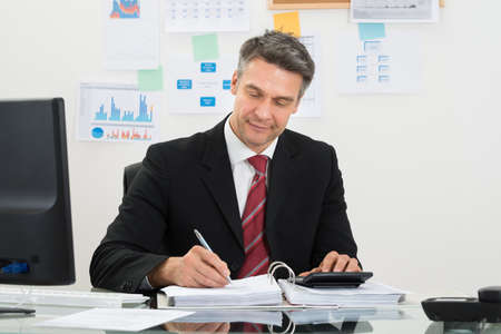 Portrait Of Mature Businessman Calculating Finance At Office Desk