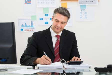 evaluacion: Retrato de hombre de negocios maduro Cálculo Finanzas En el escritorio de oficina