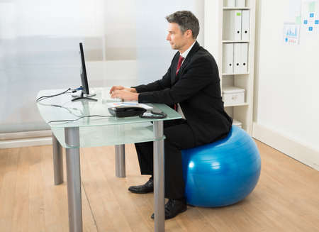 Businessman Using Computer While Sitting On Pilates Ball In Office photo