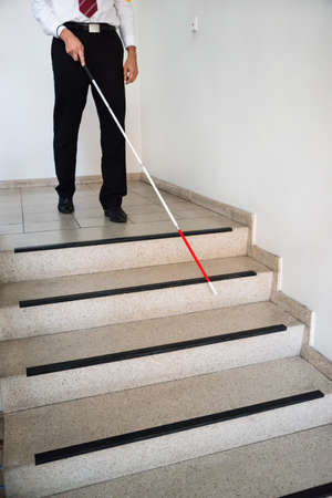 sightless: Blind Man Moving Down On Stairway Holding Stick Stock Photo