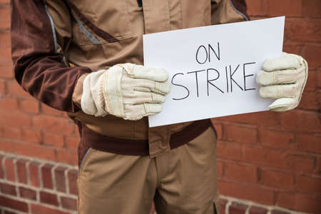 claims: Close-up Of Worker Holding Placard With The Text On Strike Written On It Stock Photo