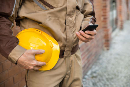 Close-up Of Builder Holding Hardhat And Using Cellphone photo