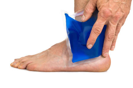 Close-up Of Hand Holding Cool Gel Pack On Ankle Over White Background Foto de archivo
