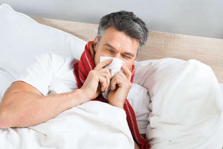Sick Mature Man Blowing His Nose While Lying On Bed At Home Stock Photo