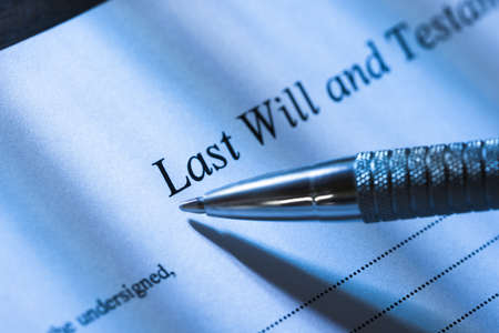 person writing: Close-up Of A Person Writing Last Will and Testament