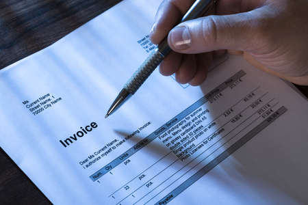 Close-up Of A Person Filling Invoice Paper With Pen Reklamní fotografie