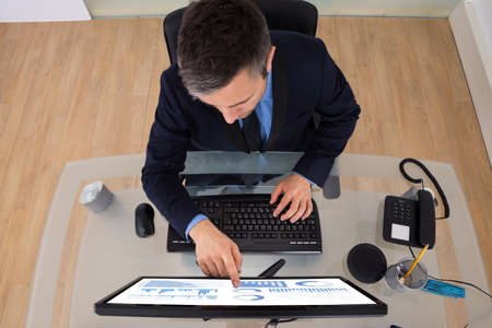 High Angle View Of Businessman Analyzing Graph On Computer Screen photo