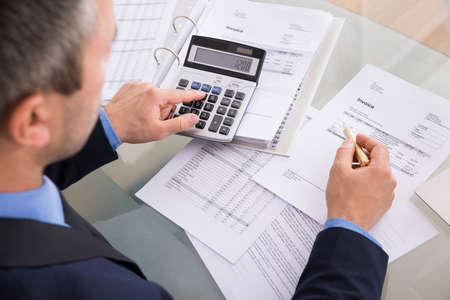 INVOICE: Over The Shoulder View Of Businessman Calculating Invoices Using Calculator Stock Photo