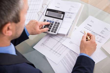 calculadora: Vista por la espalda del hombre de negocios cálculo de facturas con la calculadora