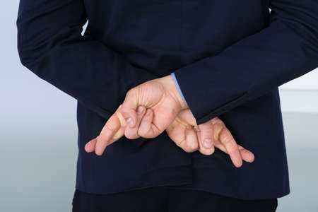 crossing fingers: Businessman Standing With Crossed Finger Behind His Back