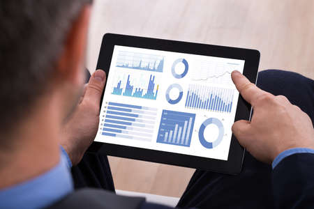 sitting man: Close-up Of Businessman Analyzing Graph On Digital Tablet Stock Photo
