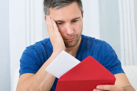perturbed: Portrait Of Unhappy Man Looking At Letter Stock Photo