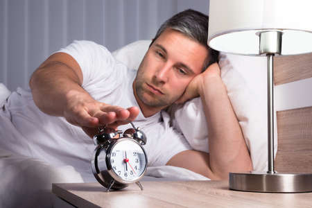 snoozing: Man Irritated With Noise Snoozing Alarm Clock