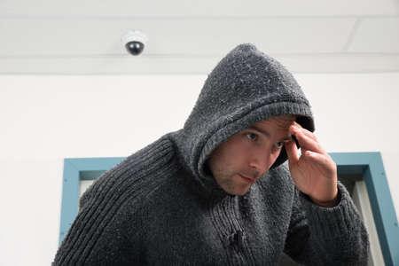 personas: Hombre en camiseta encapuchada Tratando de esconderse de las c�maras de seguridad