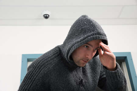 person: Man In Hooded Sweatshirt Trying To Hide From Security Camera Stock Photo