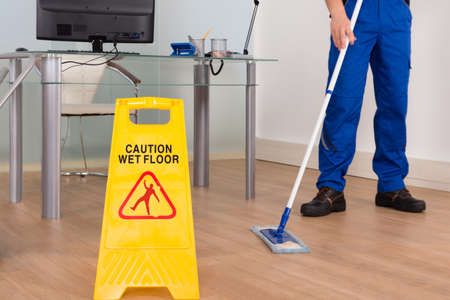 manual work: Close-up Of Janitor Mopping With Wet Floor Sign In Office