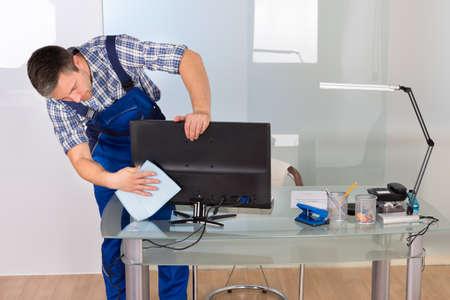 de higiene: Retrato de feliz Hombre Janitor limpieza de la computadora en el escritorio de oficina