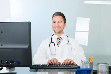 front office: Portrait Of A Smiling Male Doctor Using Computer In Clinic