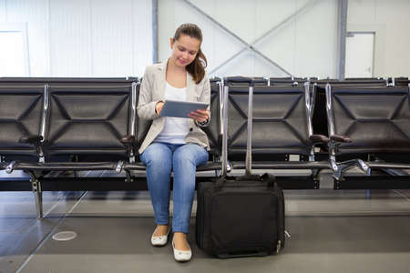 airport arrival: Full length of young businesswoman using digital tablet at airport lobby