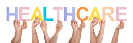 Group Of People Hands Holding Multicolored Healthcare Text Over White Background photo