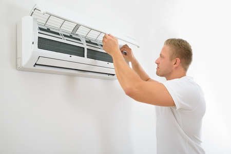 installation: Portrait Of A Young Man Adjusting Air Conditioning System
