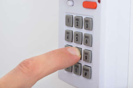 entry numbers: Close-up Of A Hand Pushing Button On Security System