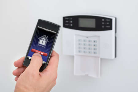 disarm: Security Alarm Keypad With Person Disarming The System With Remote Controller
