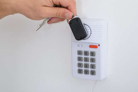 rfid: Close-up Of A Person Holding House Keys Arming A Security System Stock Photo