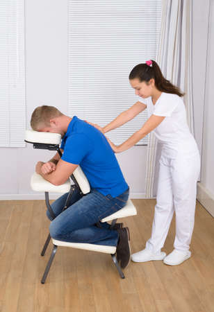 massage chair: Photo Of Young Female Massager Massaging Mans Shoulder