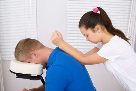 massaged: Young Man Being Massaged By A Female Physiotherapist Stock Photo