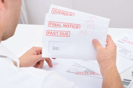 Close-up Of A Man Holding Statements Of Pending Dues