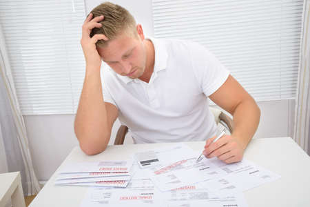 pay bill: Portrait Of A Worried Young Man Calculating Unpaid Statements Stock Photo