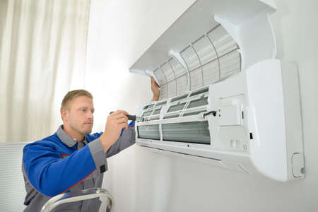 maintenance engineer: Young Man Repairing Air Conditioner Standing On Stepladder Stock Photo