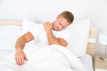 epaule douleur: Portrait d'un jeune homme assis sur le lit Souffrant de douleur à l'épaule Banque d'images