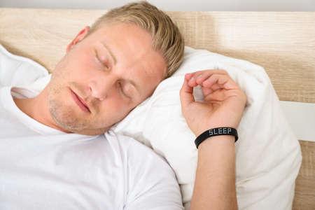 wellness sleepy: Close-up Of Young Man Sleeping Wearing Smart Wristband Stock Photo
