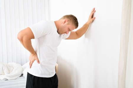 dolor espalda: Retrato del hombre joven que tiene dolor en su espalda Foto de archivo