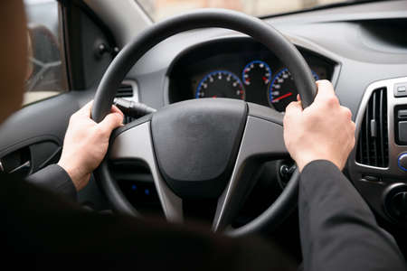 Close-up Of A Man Hands Holding Steering Wheel While Driving Car Stock Photo